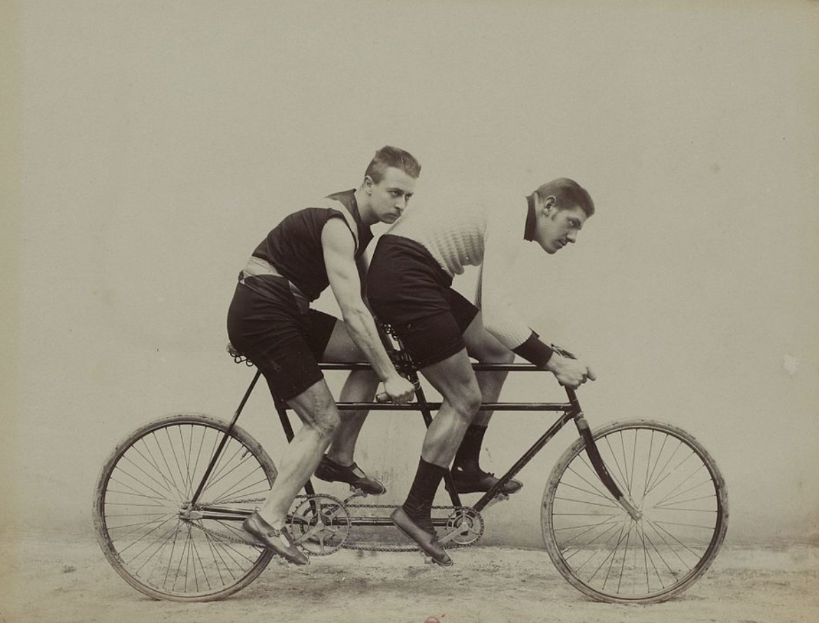 Two men riding a tandem bicycle